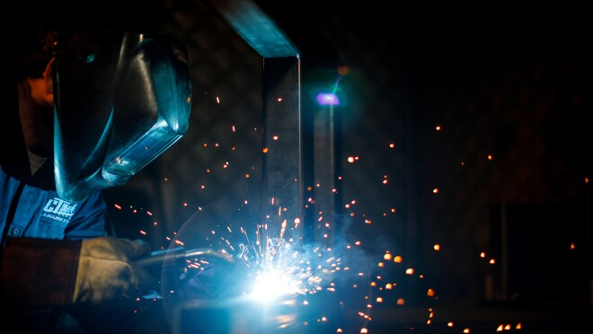 Sparks fly as a worker in safety gear uses welding equipment.