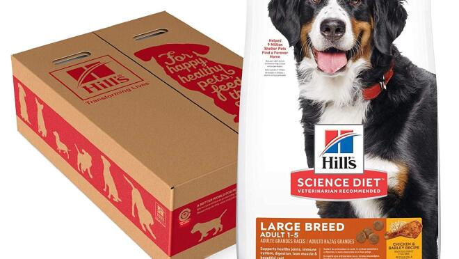A bag of Hill's dog food next to a cardboard box decorated with silhouettes of dogs.