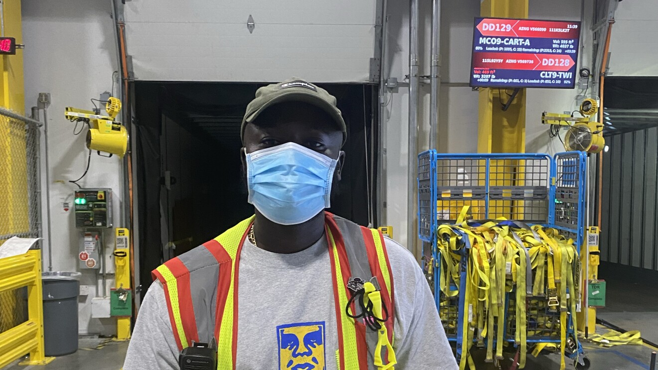 A single person in a safety vest at work with Amazon