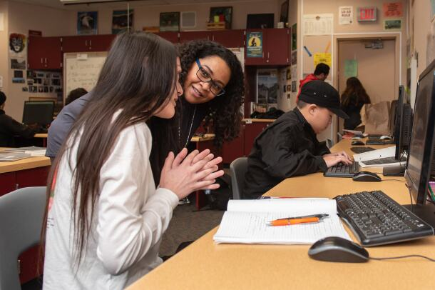 Amazonian Rovina Broomfield chats with a high school student in the classroom.