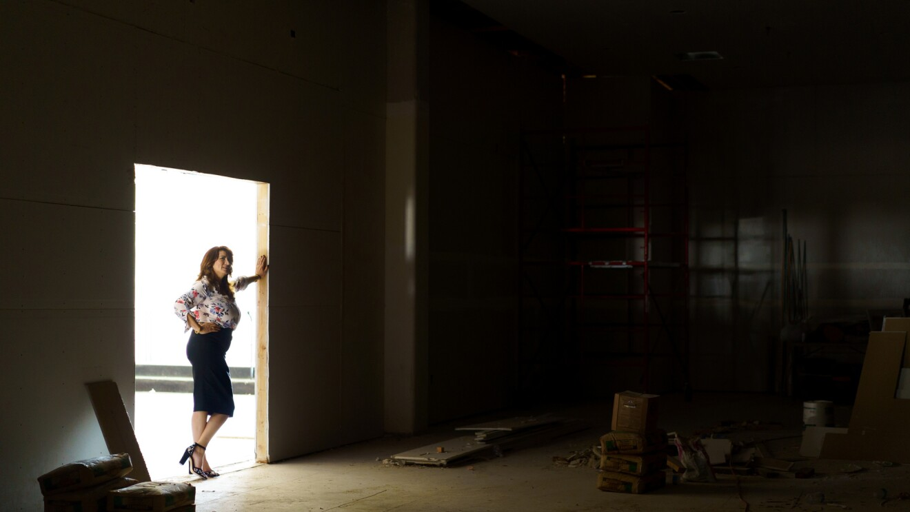 A woman stands in a doorway looking into a large room that appears to be in the final stages of construction.