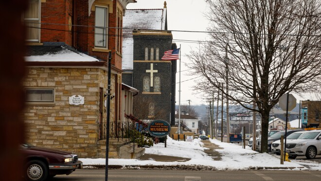 """An church and an American flag are at the center of the image. A sign in front of a stone building reads """"Salem Historical Society Museum."""""""