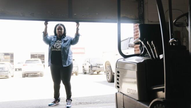 Arsha Jones opens the garage door to her warehouse where a forklift is parked.