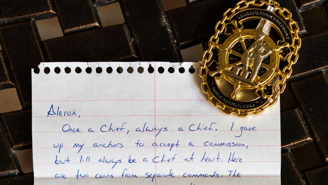 A handwritten fan letter to author Aleron Kong is shown with a military medal.