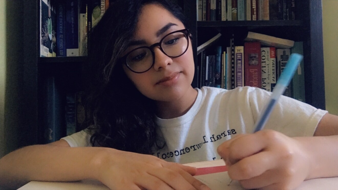 An image of a young woman writing at her desk. She is wearing glasses and a white t-shirt.