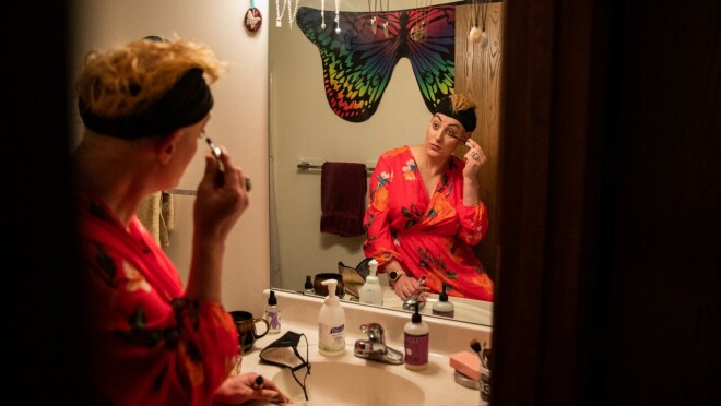 A woman sits in front of her bathroom mirror applying mascara.