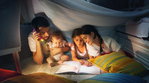 A family sits in a homemade fort, reading a book together by flashlight.