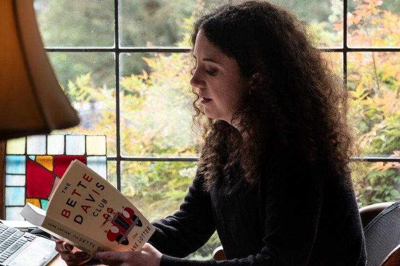 Jane Lotter's daughter, Tess, reads from her book, The Bette Davis Club. Behind her is a large window in front of greenery.