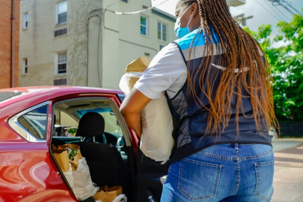 A delivery driver in an Amazon vest carries a bag of groceries to a car.