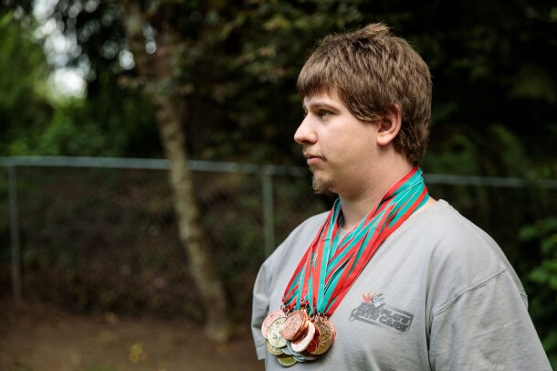 A man in a gray T-shirt stands in profile. He is wearing several medals.