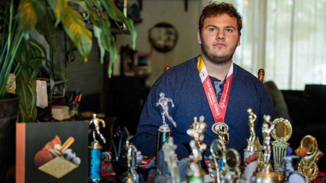 A man in a blue long-sleeved shirt wears a medal. In the foreground are many trophies.