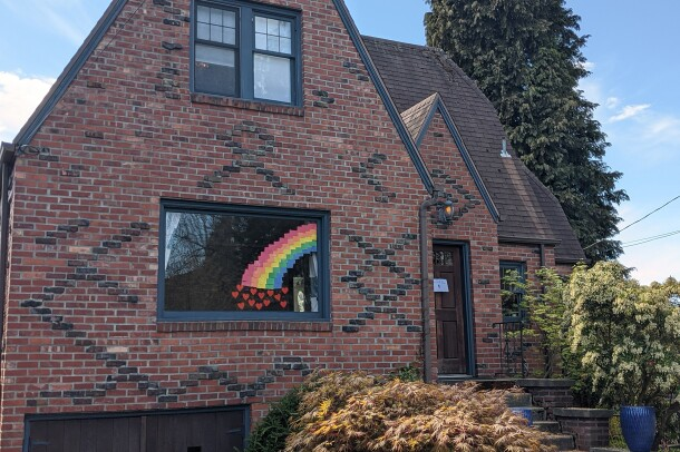 Rainbow in the front window of a brick Tudor-style home during COVID-19 pandemic.