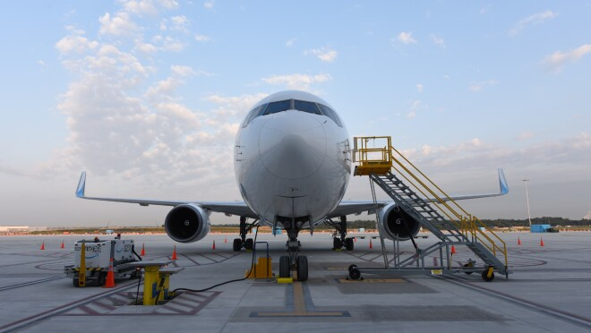 An image of the front of a Prime Air plane. There are stairs leading up to the cockpit and other equipment around the plane.