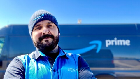 Nick Gallina wears his blue Amazon attire while smiling in front of his delivery van that features the Amazon logo.