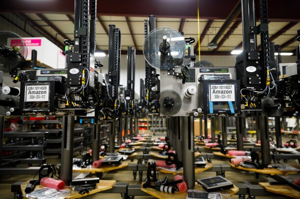 "Rows of metal machines. They have labels on them that say ""Amazon."" A series of spools of different sizes are on the machines."