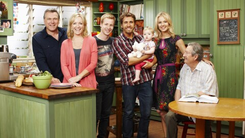 The cast of Back to the Rafters stands together in a set kitchen