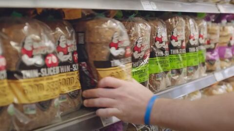 A person removes a package of bread from a shelf at a Whole Foods Market store.