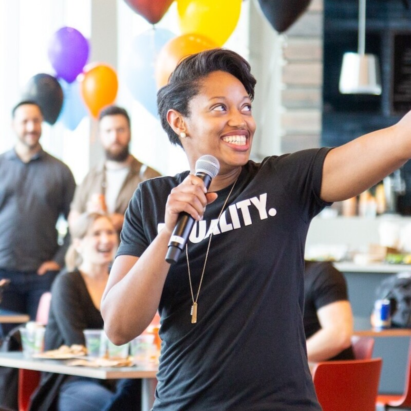 """A Black woman wearing a shirt that says """"Equality"""" speaks into a microphone while gesturing off camera. She is speaking to a brightly decorated room full of people."""