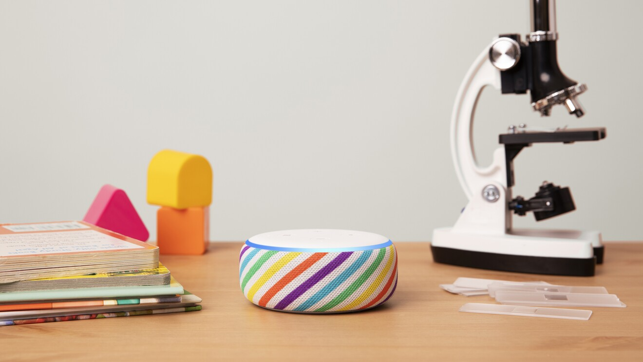 Amazon Echo Dot in rainbow stripe, displayed on a wooden tabletop. To the left are books and blocks, to the right is a microscope.