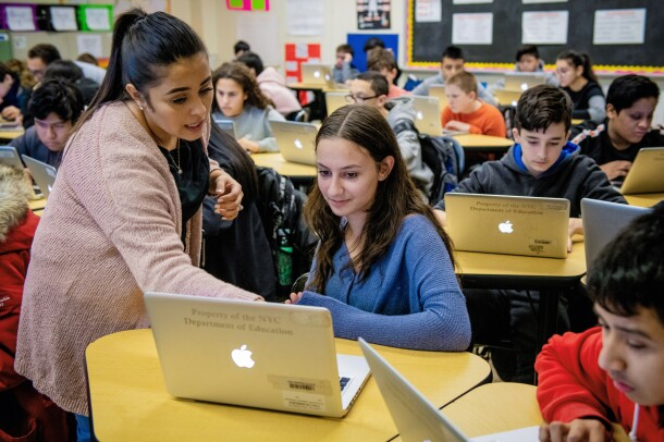 A woman leans over a student's laptop computer, as she explains something to the student. Around her are other students at their desks, working on their own laptops.