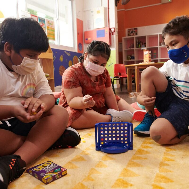 Children wear face masks and play with toys in a classroom-type setting