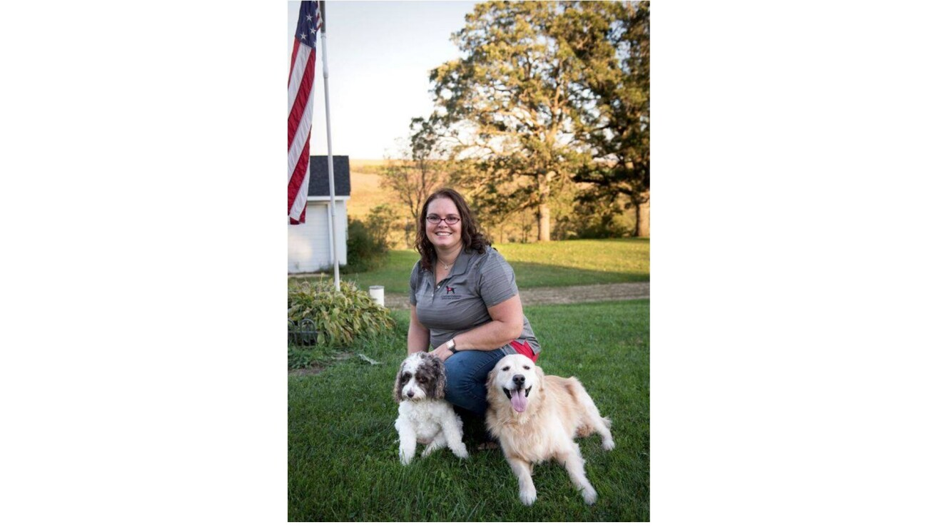 Shannon smiling and kneeling with two dogs by her side in a yard.