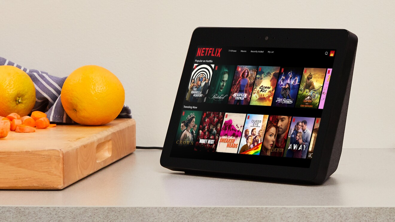 A black Echo Show sits atop a kitchen counter and displays a library of popular shows on Netflix. To the left of the device sits a cutting board with fruits and vegetables.