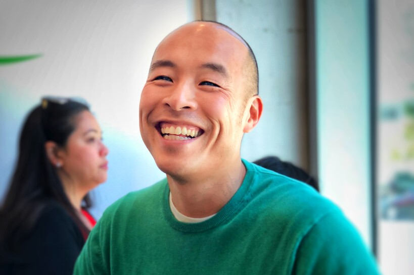 Greg Lok, CEO of Ambit, sits in a common area, smiling.