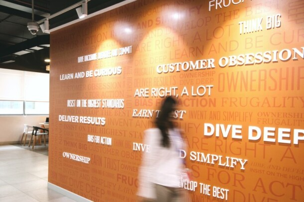 A woman walks past a wall featuring Amazon leadership principles