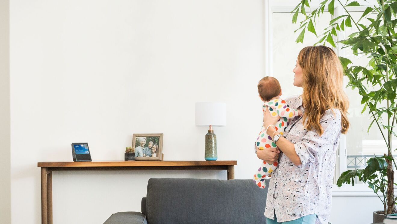 An Amazon Echo Show on a console table in a home with mom and baby