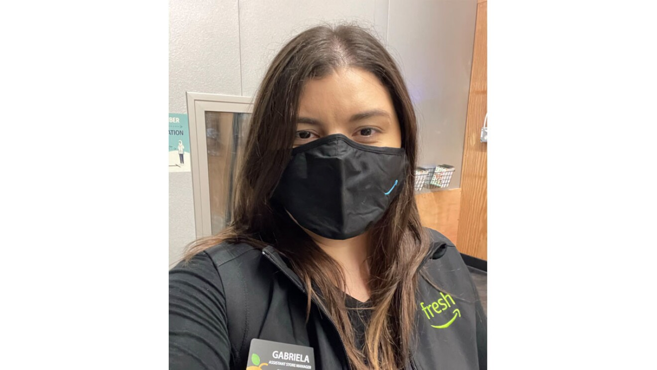 An image of a woman smiling behind a mask for a selfie photo. Her mask has the Amazon logo in the bottom right corner.