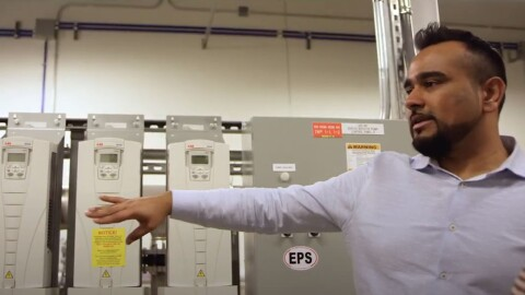 A man stands in a server room at an AWS data center. He gestures with his arm while speaking.