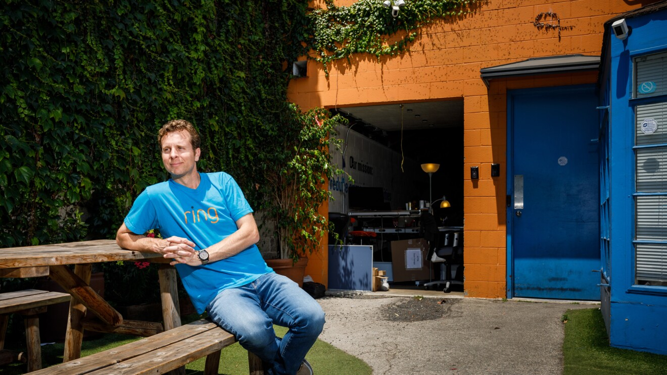 Jamie Siminoff, founder of Ring, sits at a picnic table at Ring headquarters in Santa Monica, CA. He is in a blue t-shirt and jeans, and is looking to the left.
