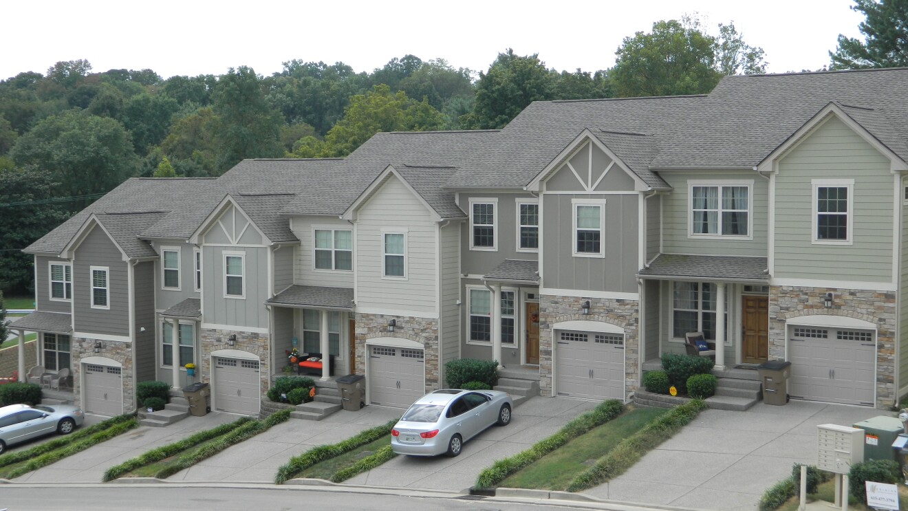 A block of connected townhouses in a neighborhood setting. Some have vehicles in their driveway.