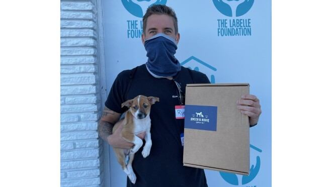 Owners hold their new adopted puppy and a Rocco & Roxie box.