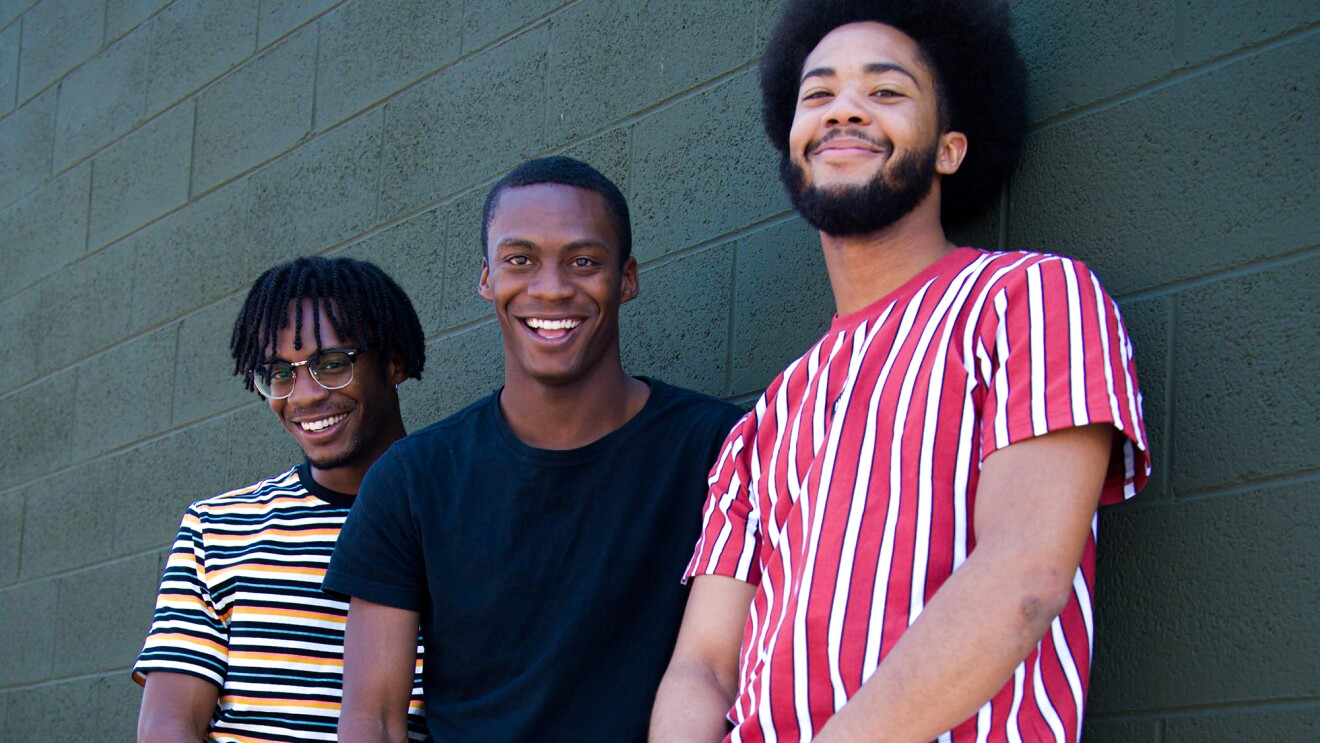 Three young Black men smile at the camera, while leaning on a cinder block wall.
