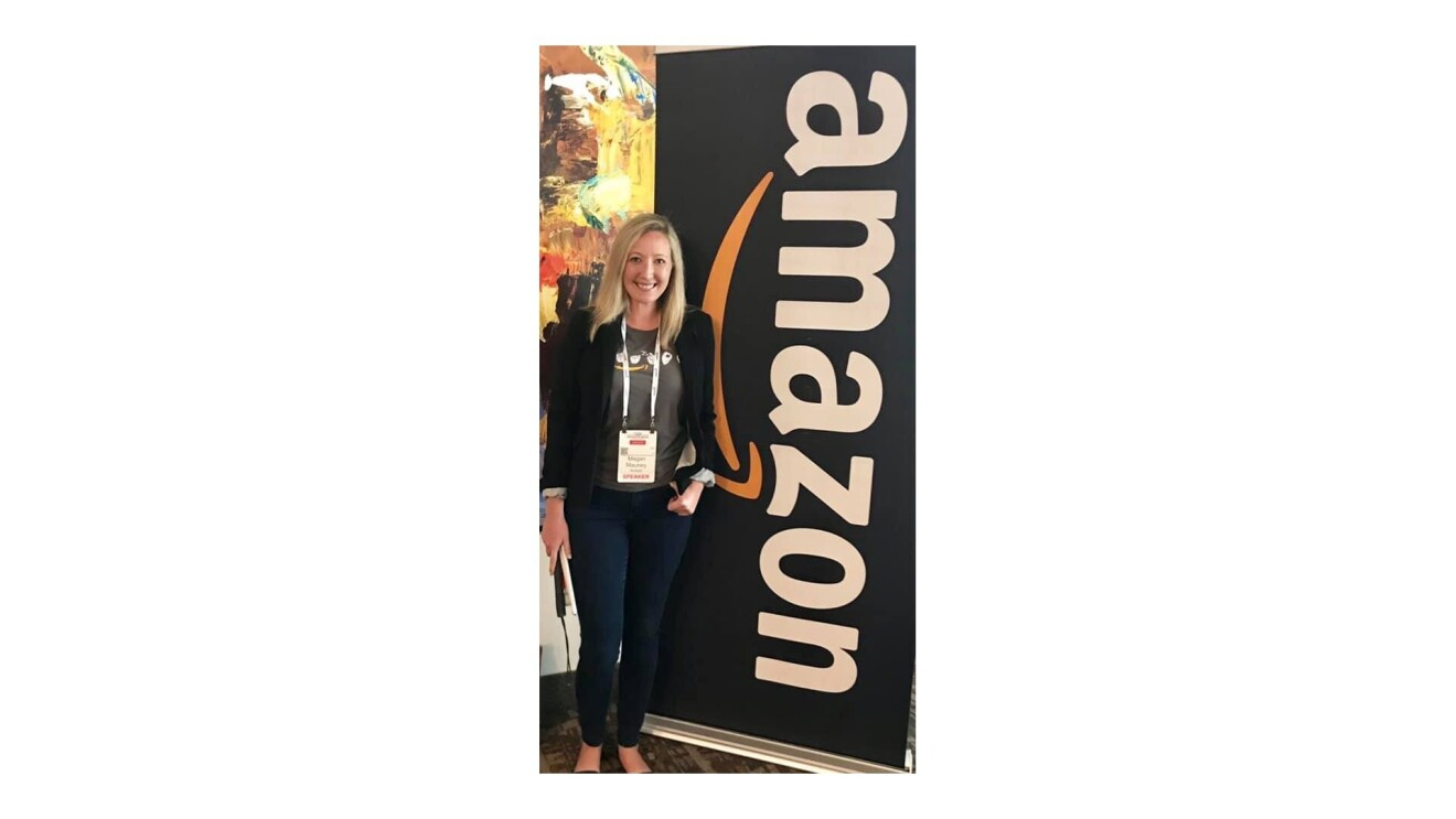 """Megan standing next to a sign that says, """"Amazon""""."""