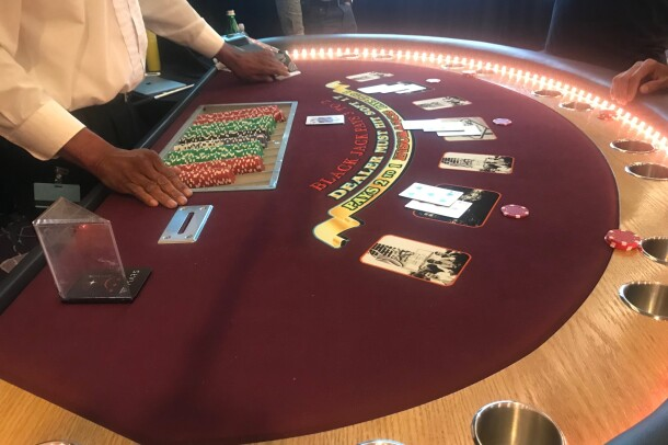 A blackjack dealer plays against three users who designed a machine learning algorithm to play the game.