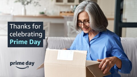 """An image of a woman smiling while opening a package. Text on the image reads """"Thanks for celebrating Prime Day"""" and there is the Amazon smile logo with the words """"Prime Day"""" above it lower down."""
