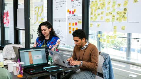 An image of two people working on laptops in a group, office setting. There are sticky notes and other paper notes on the windowed wall behind them.
