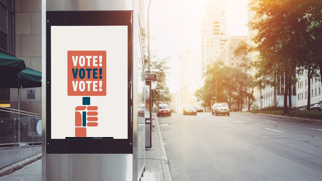 """A metal bus station on a city street, with a illustrated poster on it tyat says """"vote! vote! vote!"""""""