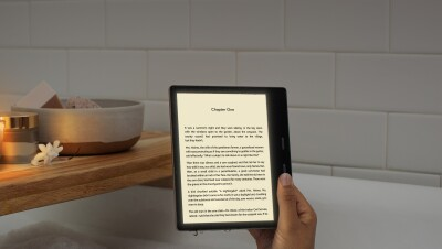 A woman holds a Kindle Oasis device with the page of a book on the display. Her arm appears from bubbles in a tub, with a wooden tub caddy behind the device.