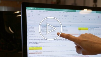 A person points to an excel sheet on a computer screen.
