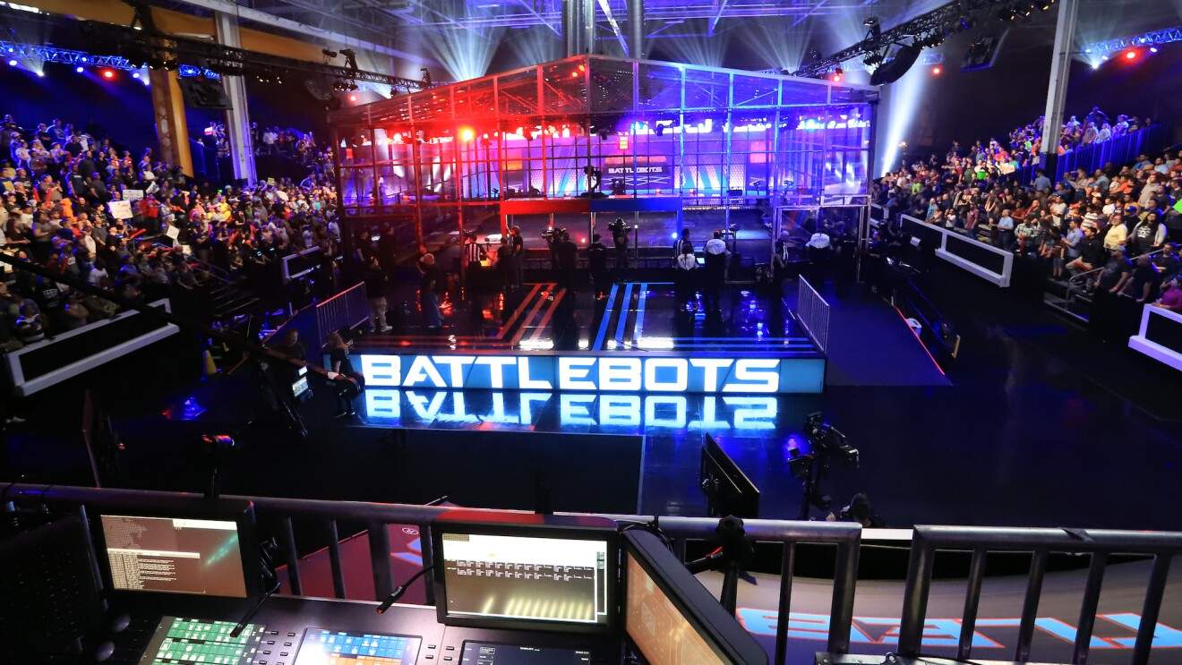 "A view inside the BattleBots arena, crowds are seen on either side of the stage, which is lit by large letters spelling ""battlebots"""