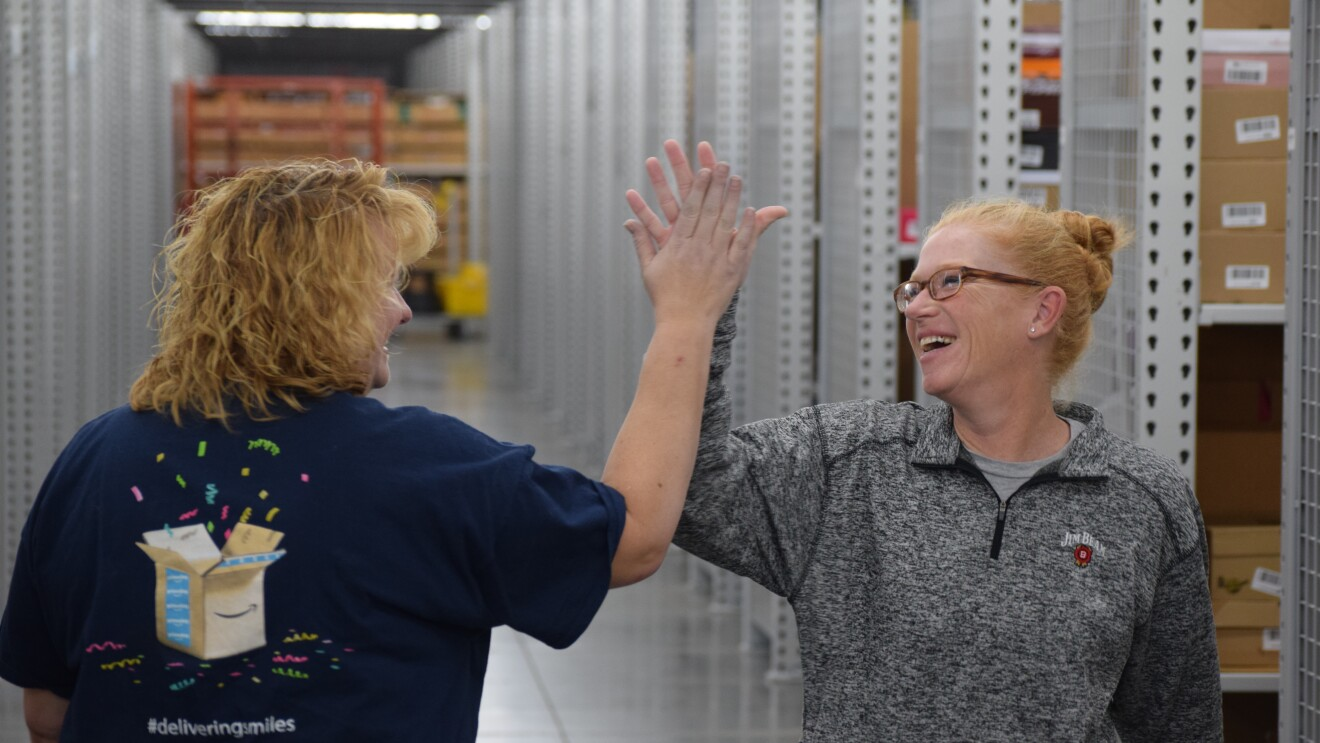 Two Amazon associates give eachother a high-five in a Fulfillment Center.