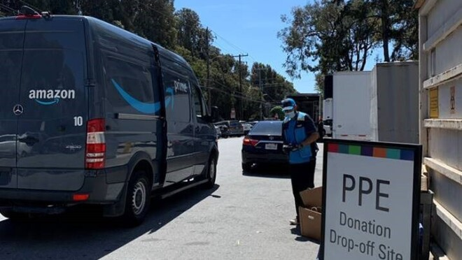 "An Amazon delivery driver and van next to a sign that says ""PPE Donation Drop-off Site."""