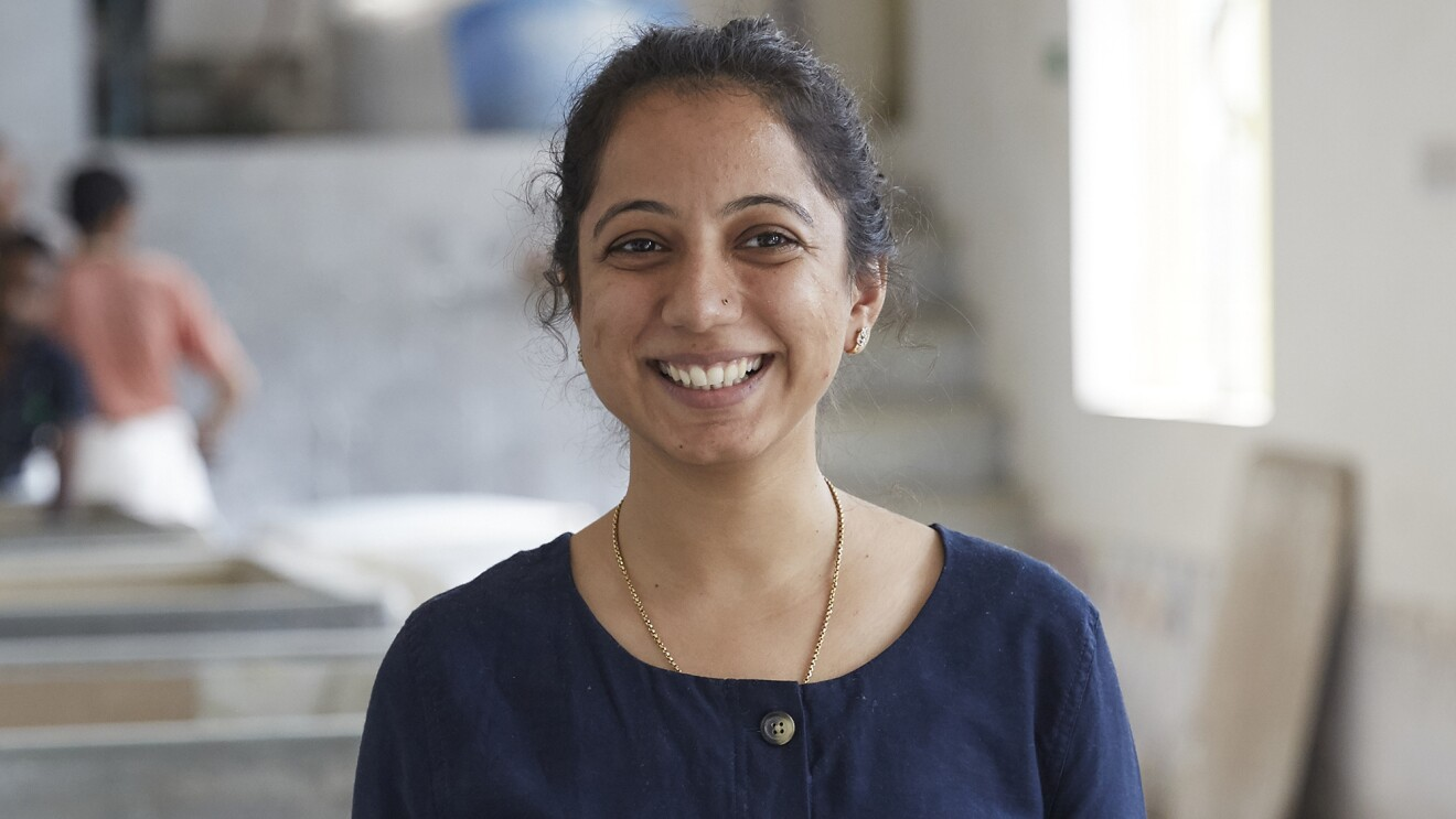 An image of a woman smiling for a headshot photo while standing in a studio space where she creates cards and stationary.