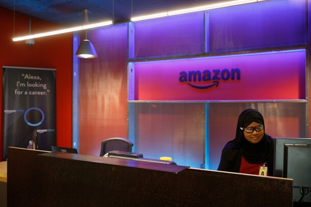 "The reception area of Amazon's Pittsburgh, PA office. There is purple accent coloring and a woman sits at a computer. The sign to the left says ""Alexa, I'm looking for a career."""