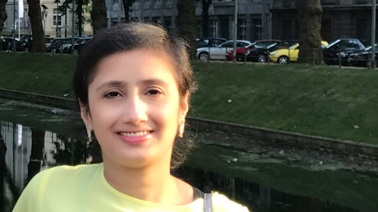 Ragini - wearing a neon yellow shirt and metallic purse leans against a ledge, smiling at the camera. Behind her are trees, and cars parked along a city street.