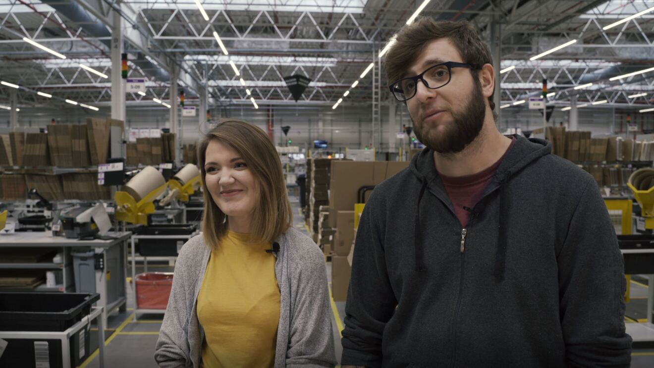arA woman stands in an Amazon fulfillment center, with a smile on her face. To her left, a man stands.